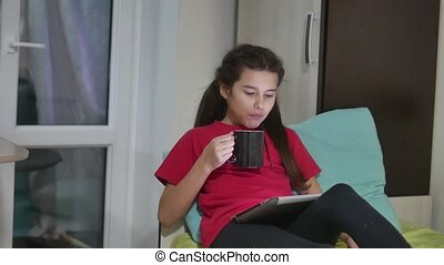 girl teen is eating sandwich plays in a tablet draws on a online game. girl child indoors social media tablet internet drinking tea slow motion video