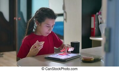 girl teen is eating sandwich plays in a tablet draws on a online game. girl child social media tablet internet drinking indoors tea slow motion video