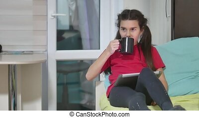 girl teen is eating sandwich plays in a tablet draws on a online game. girl child social media tablet indoors internet drinking tea slow motion video