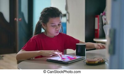girl teen is eating sandwich plays in a tablet draws on a online game. girl child social media tablet internet drinking tea slow motion indoors video