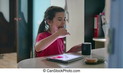 girl teen is eating sandwich plays in a tablet draws on a online game. girl child social media indoors tablet internet drinking tea slow motion video