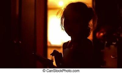 girl teen looking game smartphone on the Internet in the corridor indoor yellow brown silhouette