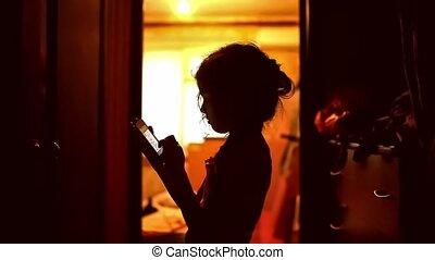 girl teen looking smartphone game on the Internet in the corridor indoor yellow brown silhouette