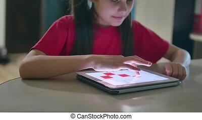 girl teen plays in a tablet draws on a online game. girl...