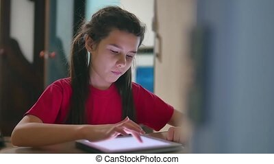 girl teen plays in a tablet online game. girl child social...