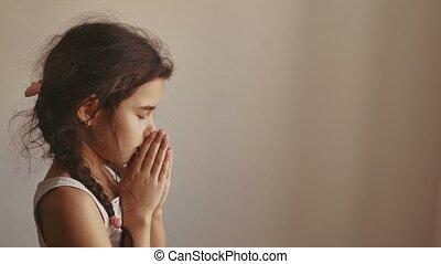 girl teen praying on a black background - woman praying on a...