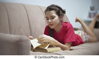 girl teen reading a book lying on sofa indoors. girl kid...