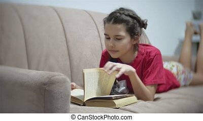 girl teen reading a book lying on sofa indoors. girl kid reading a book lying on a sofa