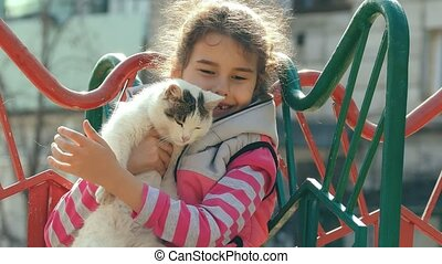 girl teen stroking cat on outdoors playground - girl teen...