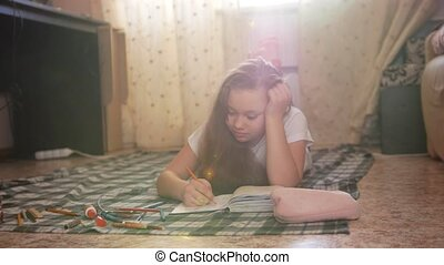 Girl teen who spend time at home drawing while lying on the...