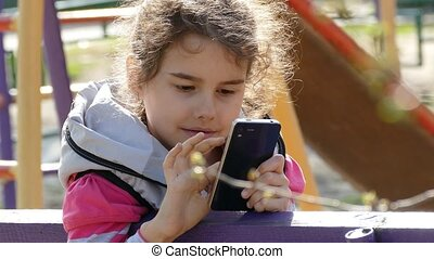 girl teen with a smartphone on the playground