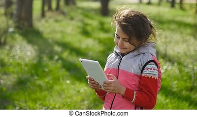 girl teen with a tablet in spring on background of green grass in the forest plays in the online game