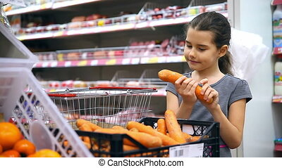 girl teen with in supermarket to buy carrot vegetables -...