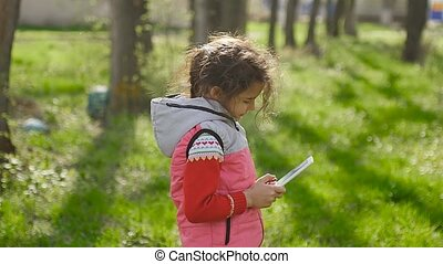 girl teen with tablet in spring on background of green grass in forest plays in the online game