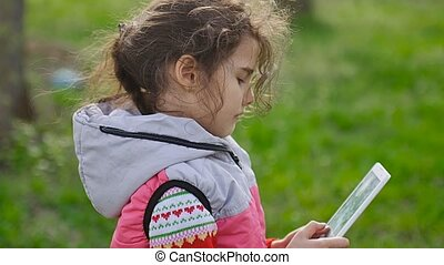 girl teen with tablet in spring on background of green grass in the forest plays in the online game