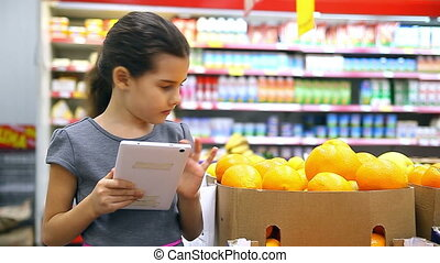 girl teen with tablet in the supermarket to buy orange