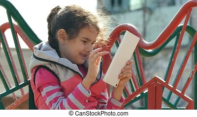 girl teen with the tablet on the playground outddors