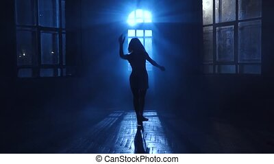 Girl teenage dances the moonlight penetrates through the window. Silhouette