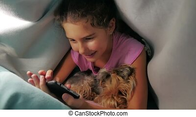 girl teenager and dog under a blanket playing in a...
