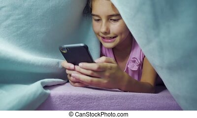 girl teenager and dog under a blanket night playing in a...