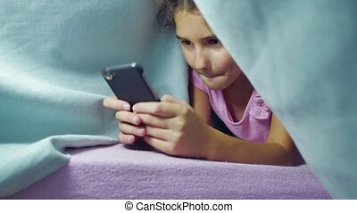 girl teenager and dog under a night blanket playing in a...