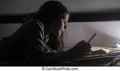 girl teenager and smartphone. little teen hood girl writes a...
