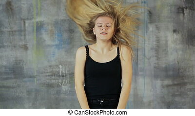 Girl teenager blonde dancing dance with her hair rotating her head.
