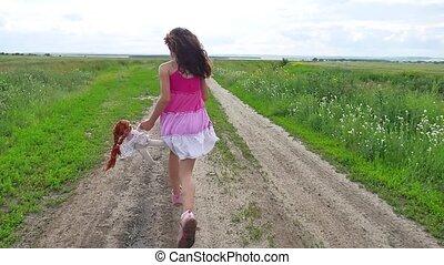 Girl teenager childhood. Girl teenager with doll running...