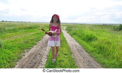 Girl teenager childhood. teenager girl with a doll running down the road in nature in the field.