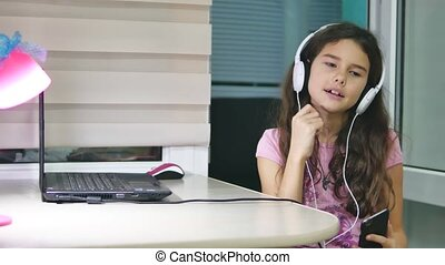 girl teenager dancing and singing in music headphones. schoolgirl listens to music online and dances and indoors sings