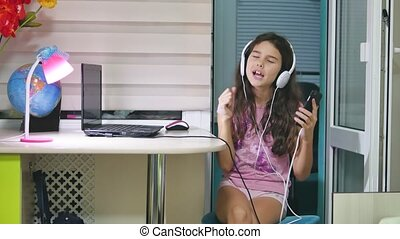 girl teenager dancing and singing in music headphones. schoolgirl listens to music online and dances indoors and sings