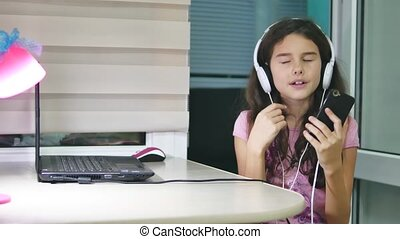 girl teenager dancing and singing in music headphones. schoolgirl listens to music online and dances and sings indoors