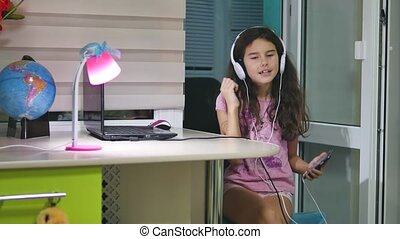 girl teenager dancing and singing in music headphones. schoolgirl listens to music online and indoors dances and sings