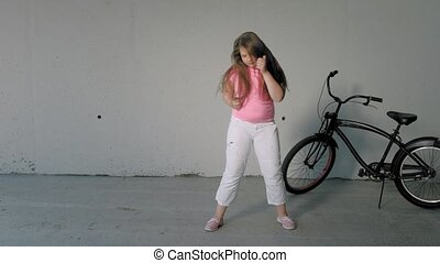 Girl teenager dancing on a gray background. Street dance -...