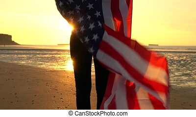 Girl teenager female young woman wrapped in an American US Stars and Stripes flag on a beach at sunset or sunrise