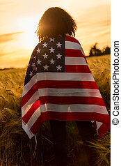 Girl Teenager Female Young Woman Wrapped in USA Flag in Field at Sunset