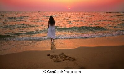 girl teenager in a long white dress with long hair walks along the seashore at sunset