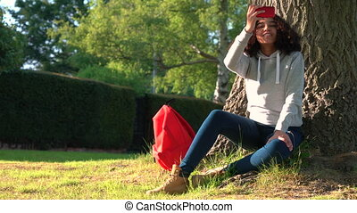 Girl teenager leaning against a tree with a red backpack and using a cell phone camera to take pictures and social media