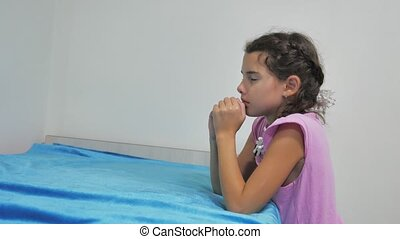 girl teenager prays before bedtime. kneeling by the bed of a...