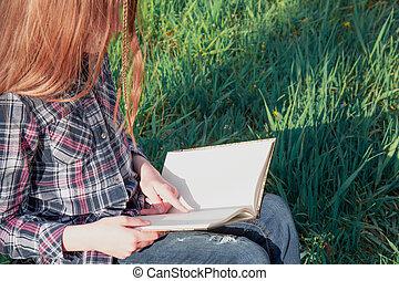 Girl teenager reads book outdoor