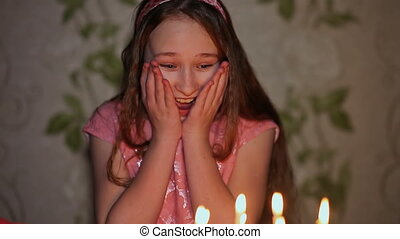 Girl teenager seeing a cake and admires extinguishes candles. Birthday Celebration