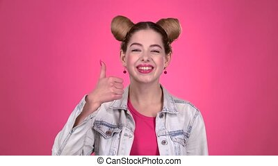 Girl teenager shows thumbs up. Pink background