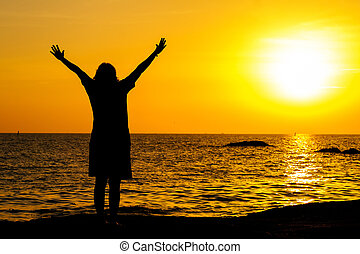 Girl teenager standing in the water with a raised hands at sunset