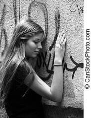 The young girl with phone on a background of a wall with graffiti