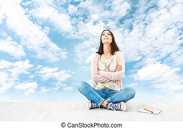 Girl teenager thinking inspiration or planning idea, sitting over blue sky background