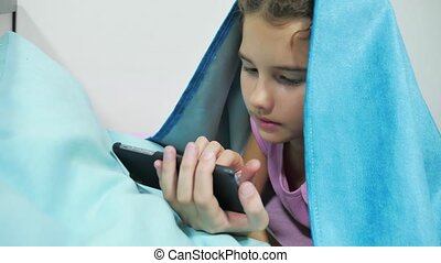 girl teenager under a blanket playing in a smartphone....