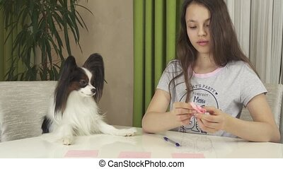 Girl teenager with dog Papillon guess on desires, writes...