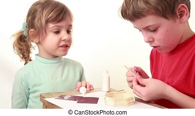 Girl tell something boy which apply glue on stick and attach...