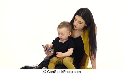 Girl tells and shows something on the smartphone to her child. White background