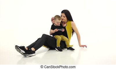 Girl tells and shows something on the smartphone to her child. White background. Slow motion